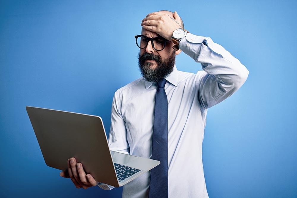 Mann hat Haarausfall und sucht im Internet